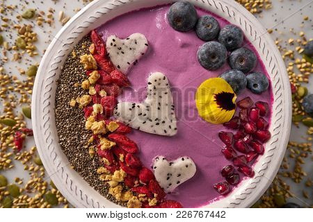 Acai bowl smoothie pitaya hearts blueberry goji chia pomegranate and seeds for Valentines day