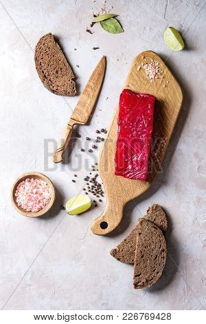 Piece Of Beetroot Marinated Salted Salmon With Sliced Rye Bread, Pink Salt, Pepper And Lime Served O