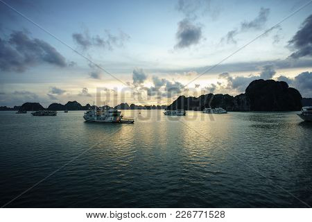 Halong Bay At Sunset With Tourist Cruise Ships And Rocky Islands. Popular Landmark, Famous Destinati