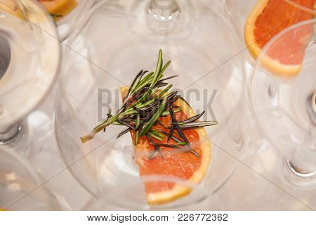 A Glass With A Grapefruit Slice And Rosemary. Rosemary Grapefruit..