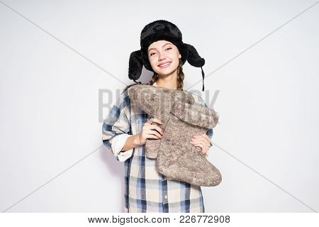 Happy Russian Beauty Girl Wearing A Hat With Ear-flaps Holds Warm Felt Boots