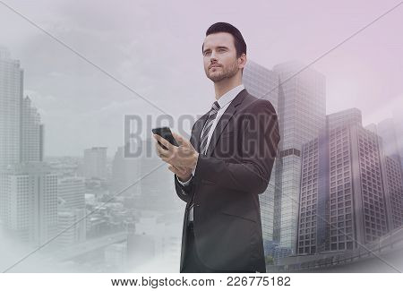 Double Exposure Of A Businessman And City Using Mobile Phone. Technology Media.
