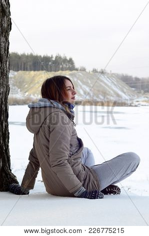 A Young Caucasian Girl In A Brown Coat Staring Into The Distance On The Horizon Line Between The Sky