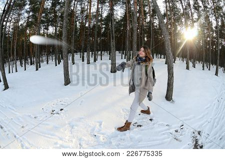 A Young And Joyful Caucasian Girl In A Brown Coat Is Throwing A Snowball In A Snow-covered Forest In
