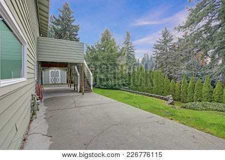 Backyard View Of Two Story Home With Spacious Patio Are