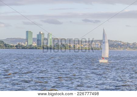 Sailboat At Sunset In Guaiba Lake With Buildings And Trees