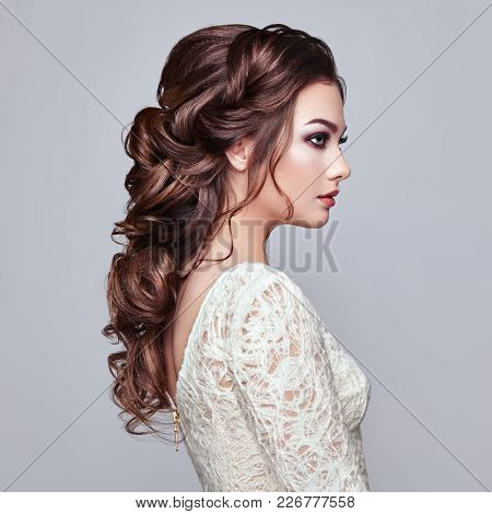 Brunette Woman With Long And Shiny Curly Hair. Beautiful Model Lady With Curly Hairstyle. Care And B