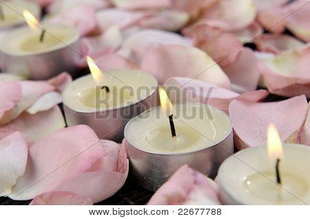 Romantisches stilleben - brennende Kerzen und Rosenblüten