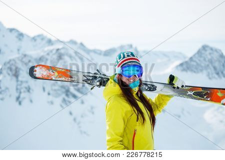 Photo of athlete woman with skis on her shoulder against background of snowy hill