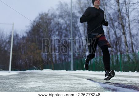 Image of running sporty man in sneakers in stadium against background of trees on winter evening