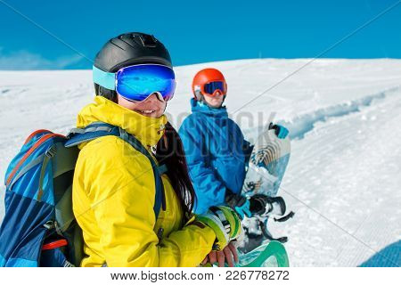 Image of happy couple with snowboard on background of snowy hills