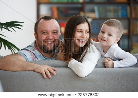 Image of smiling parents with son sitting on gray sofa