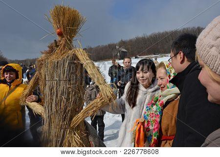 People Near Straw Scarecrow