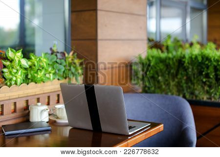 Close Up Laptop On Restaurant Table Without People. Teapot, Cup And Black Notebook At Catering Estab