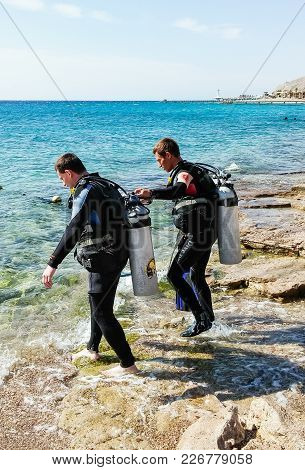 Eilat, Israel, March 13, 2015 : Two Scuba Divers In Suits For Scuba Diving Go To The Water Near The