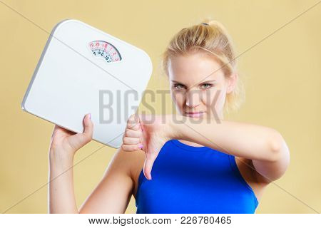 Frustrated Sad Blonde Girl Holding Scales, Making Thumb Down Gesture Sign. Weight Gain, Time For Sli