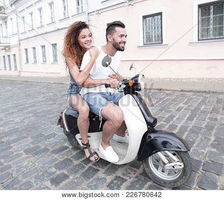 Full length side view of happy couple riding on retro motorbike