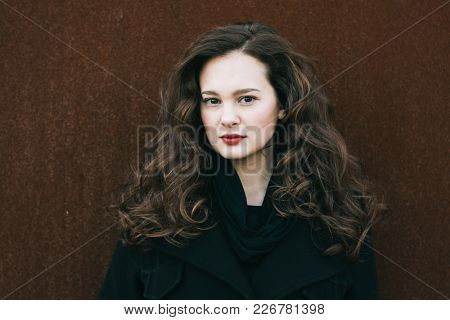 Beautiful long hair woman outdoor portrait. 20-29 years old woman looking at camera. Long haired girl portrait. Ideal for social media profile.