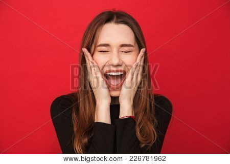 Photo of screaming excited young woman standing isolated over red background. Eyes closed.
