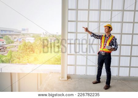 Middle Aged Asian Architect, Engineer Or Technician Man With Safety Helmet Holding Blueprint And Poi
