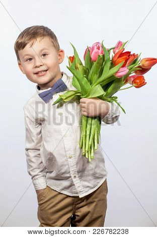 Cute Little Boy Holding A Bouquet Of Flowers. Tulips. Mothers Day. International Women's Day. Portra