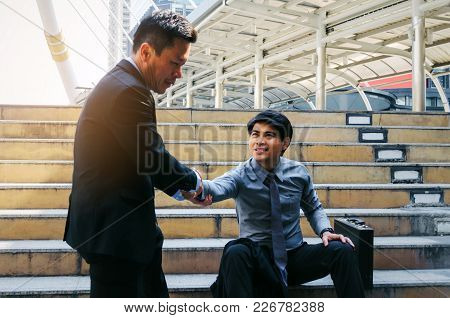 Medium Aged Asian Business Man Helping A Friend In Pulling Hand With Man Upset About Life Problems S