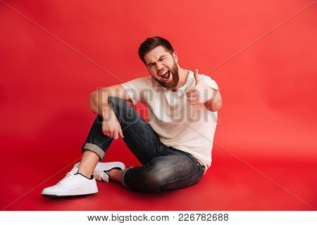 Photo of excited bearded man sitting on floor isolated over red background wall. Looking camera showing thumbs up.