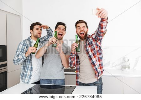 Portrait of a three excited male friends celebrating while standing with beer bottles and taking selfie indoors