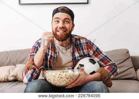Image of excited football lover sitting at home and watching game in cap and plaid shirt with pop corn and ball in hands