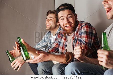 Photo of satisfied bachelors shouting happily while partying at home and watching football game with drinking beer