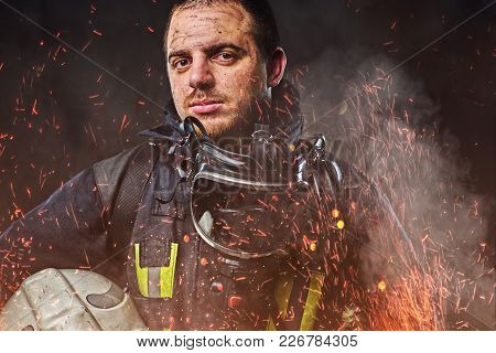 A Professional Firefighter Dressed In Uniform Holding Safety Helmet In Fire Sparks And Smoke Over A