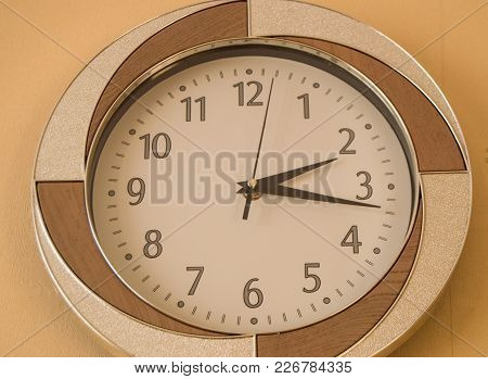 Round Wall Clock Shows The Time 2 Hours And 15 Minutes On Light Dial.