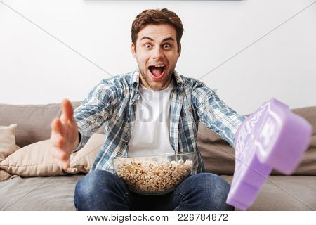 Photo of unshaved man resting alone at home and watching game with big toy glove and pop corn