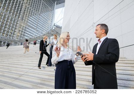 Foreign Managers In Official Journey Speaking On Stairs With Tablet And Document Cases. Concept Of B
