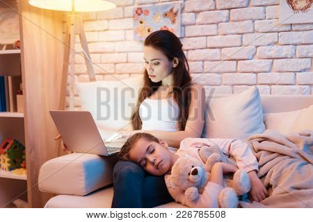 Daughter Is Sleeping On Mother's Lap While She Is Reading On Laptop Late At Night At Home.