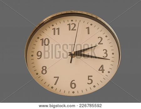 Round Wall Clock Shows The Time 2 Hours And 15 Minutes, The Dial Isolated On Gray Background.