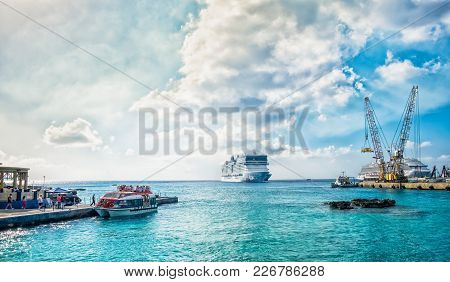 George Town, Grand Cayman, Feb 2018, Port With A Cruise Ship Leaving And Tourists Embarking On A Mar