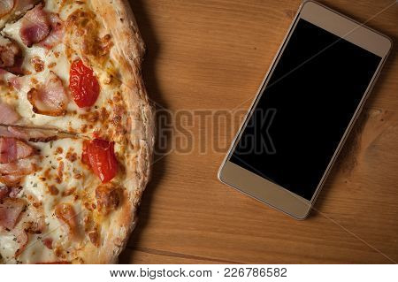 Food Delivery And Online Order Concept. Fresh Italian Pizza And Smartphone On Wooden Table. Place Fo