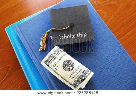 Scholarship Graduation Cap With Money On A Pile Of Books