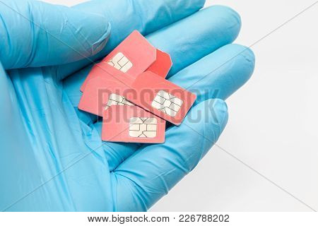 Hand In Blue Glove Holding Sim Card On White Background