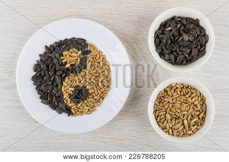 Plate With Fried Peeled And Unpeeled Sunflower Seeds In Form Yin-yang And Bowls With Seeds On Wooden