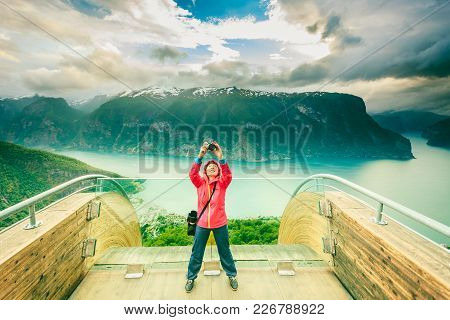 Tourism And Travel. Woman Tourist Nature Photographer Taking Photo With Camera, Enjoying Aurland Fjo