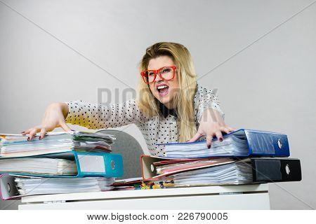 Focused Business Woman Feeling Energetic Sitting Working At Desk Full Off Documents In Binders.