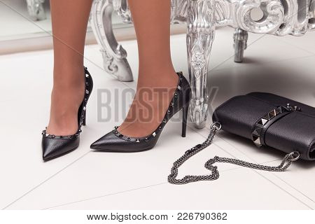 A Girl In Fashionable Shoes With A Bag. Girl In High-heeled Shoes.