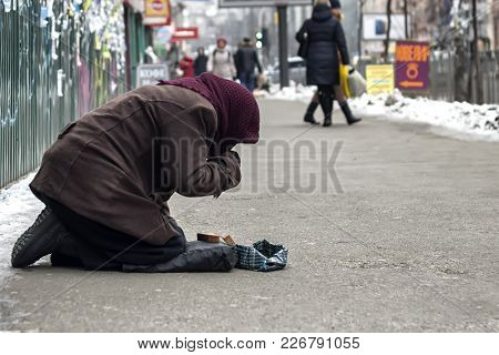 An Elderly, Homeless Woman Asks For Mercy From Indifferent Passers-by. The Concept Of Poverty, Indif