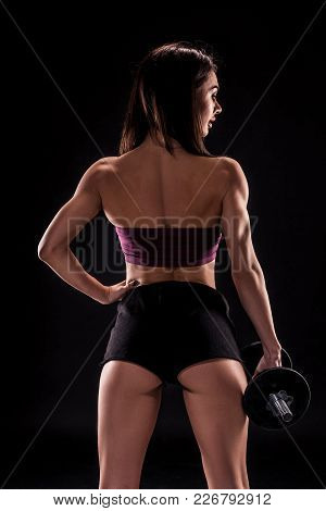 Strong Muscular Young Woman Holding Dumbbells At Her Side Standing With Her Back To The Camera Looki