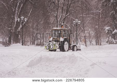 The Tractor Cleans The Snow In The Park