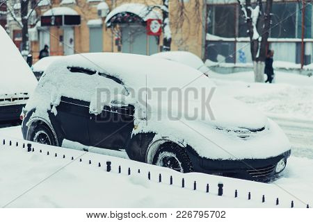 Parked Car Stands Along The Road All In The Snow