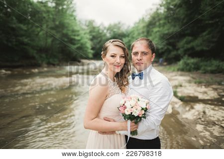 Beautifull Wedding Couple Kissing And Embracing Near The Shore Of A Mountain River With Stones.