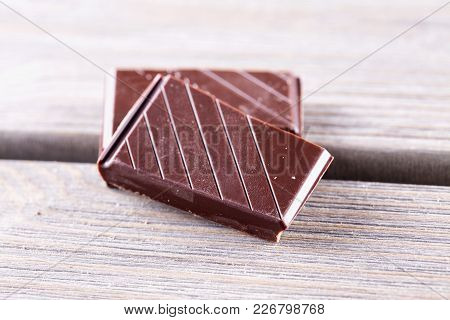 Chocolate Blocks Over Wooden Table